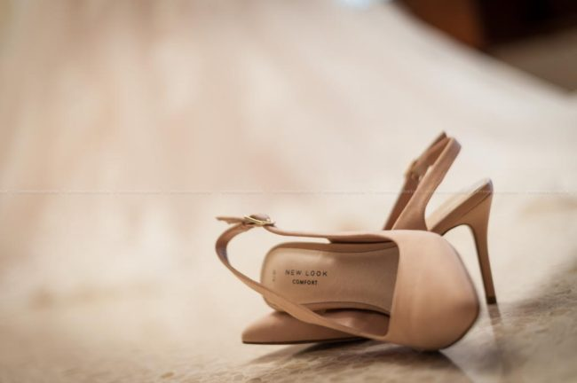 Photo of the bridal shoes, with the wedding dress in the background