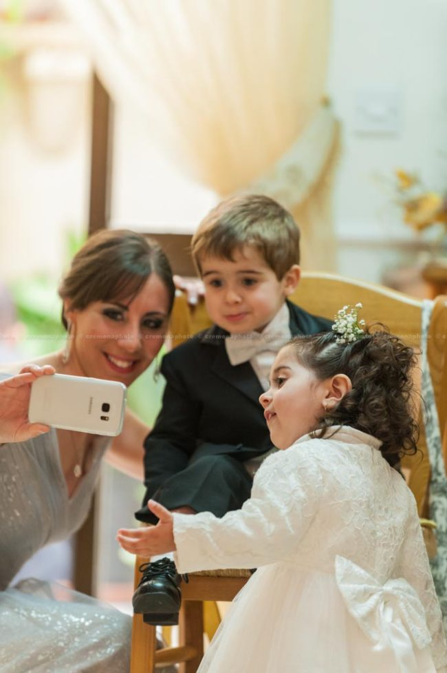 A wedding bridesmaid showing a picture she just took to her toddler nephew and niece