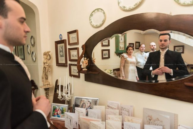groom getting ready in front of the mirror, with his family observing him from behind
