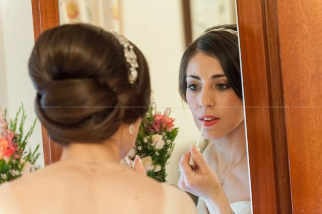 The bride applying a final touch of make up prior to leaving her home to get married in Gozo