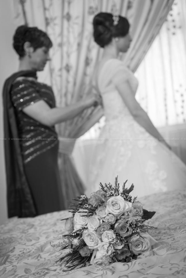 A flower bouquet is laying on the bed, with mother helping her daughter into the bridal dress
