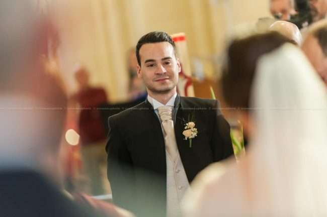 Red eyes betraying groom's emotion while his bride is walking down the aisle prior to wedding.