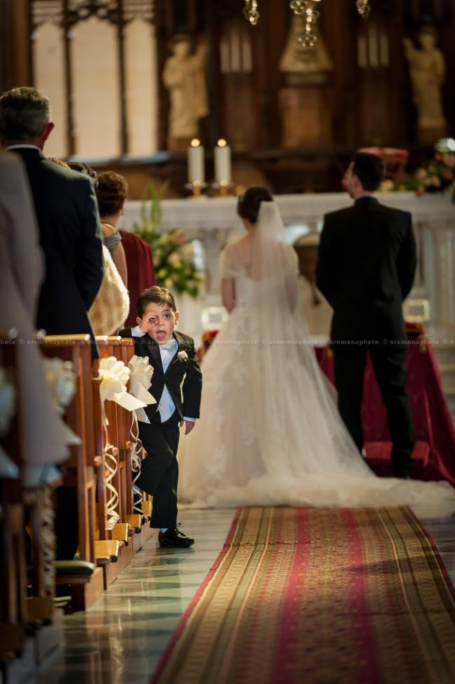 A young page boy pulling up a silly face, behind the back of the bride and groom