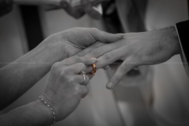 black and white picture of the ring being placed into the groom's finger, during the wedding vows
