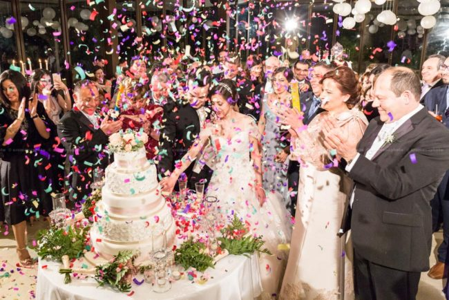 Bride and groom cutting the wedding cake surrounded by family, friends and a rainfall of colorful paper confetti