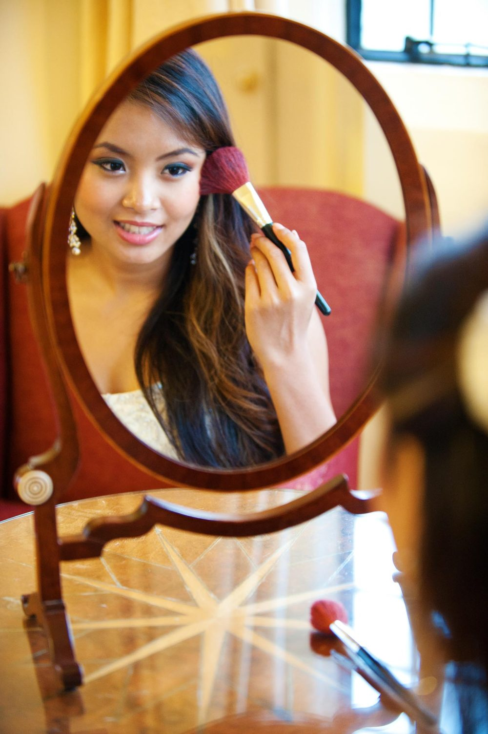 Bride applying make up in front of a table mirror at her room before the wedding